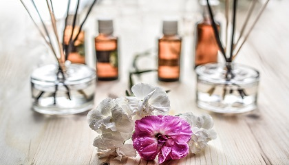 Beauty oils, diffusers and flowers on a wooden table